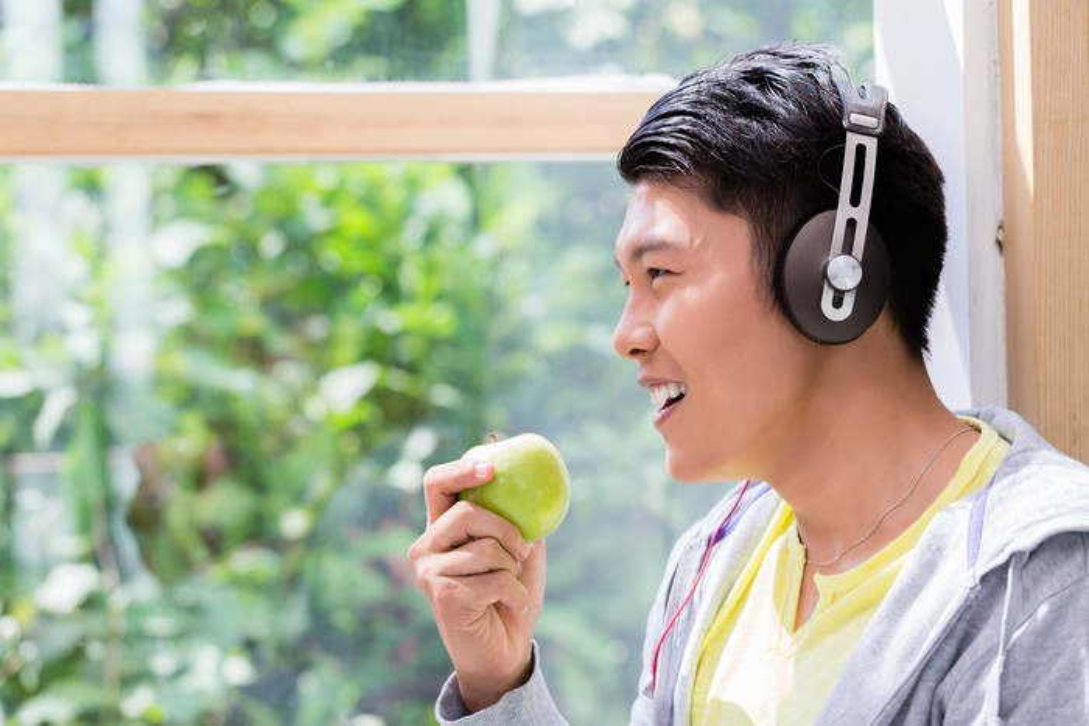 A man wears headphones while eating an apple.