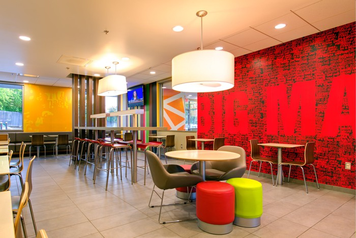 Interior view of a remodeled McDonald's with modern lamps hanging from the ceiling, modern seating, and a flat-screen TV on the wall.