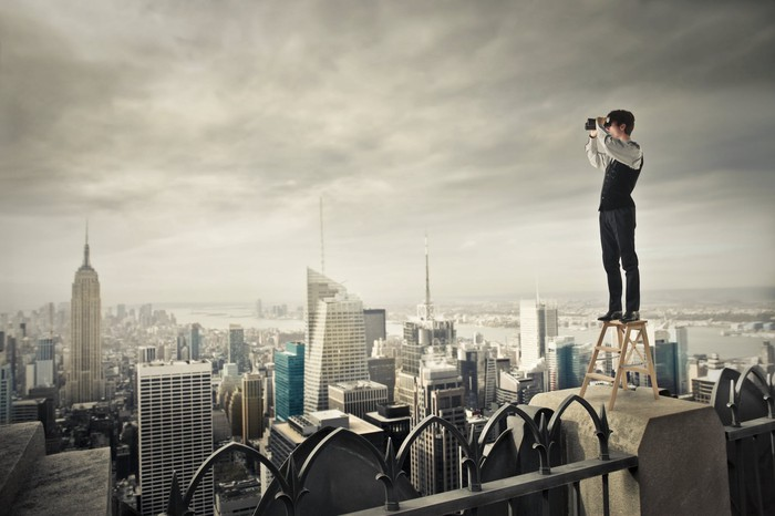 Businessman standing on top of a step ladder on a skyscraper roof looking through binoculars.
