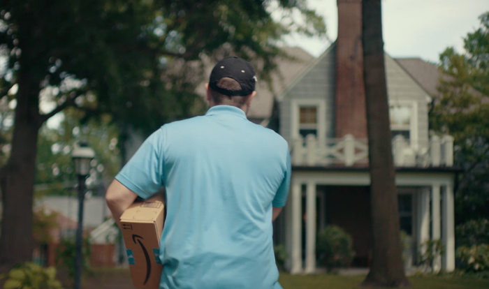 Man in light blue shirt carrying an Amazon package and walking toward a gray house.