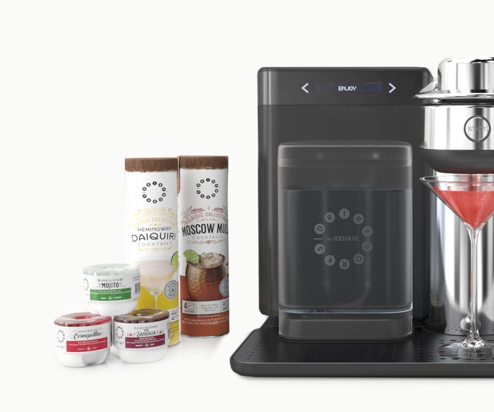 A Drinkworks Home Bar by Keurig with various cocktail mixes on the side.