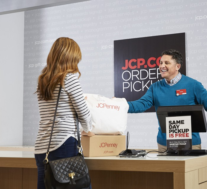 Employee helping woman at J.C. Penney's online order pickup desk