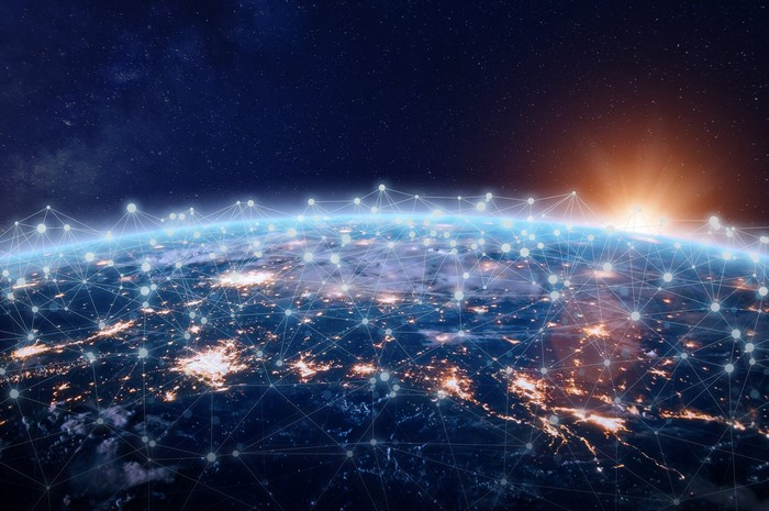 Aerial view of Earth at night with connected wireless nodes, AI/Internet of Things concept