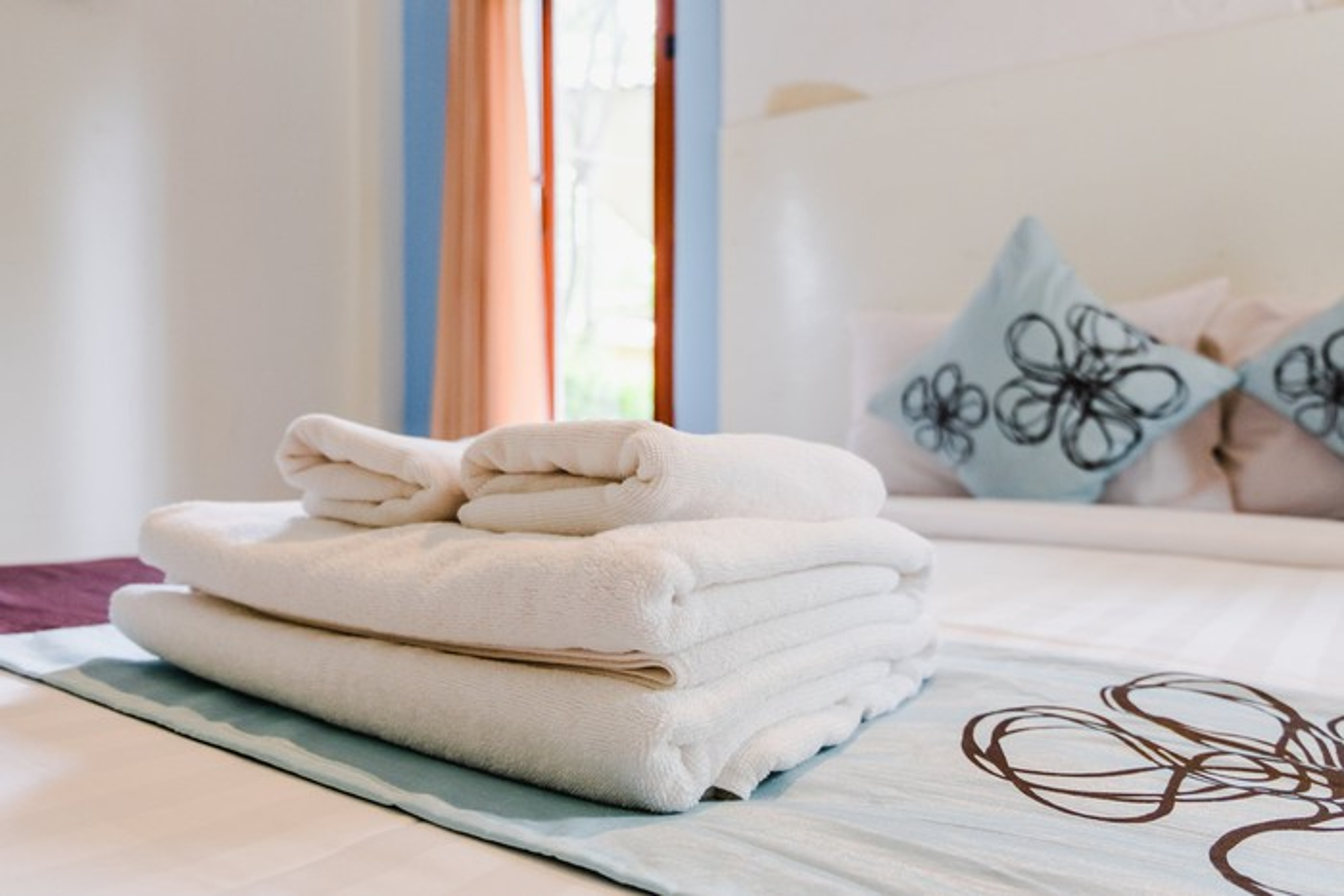 Towels folded on bedspread.