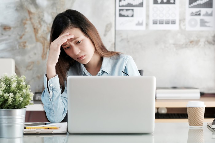 Woman at a laptop looking distressed.