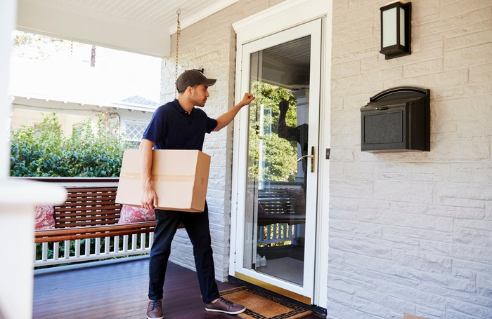 A deliveryman knocking on a door with a package.