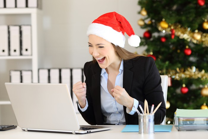 A woman in a Santa hat laughs at a ccomputer screen; a Christmas tree is in the background.