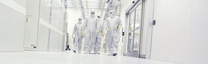 Employees in white full body protective gear walk through the hallways of a research plant.