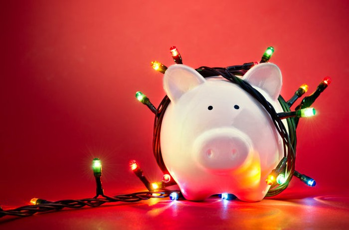 A piggy bank wrapped in Christmas lights.