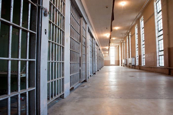 A long hallway in a prison with a row of cells to the left.