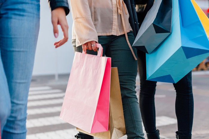 A woman walks with shopping bags.