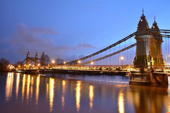 View of suspension bridge over the river Thames at dusk.