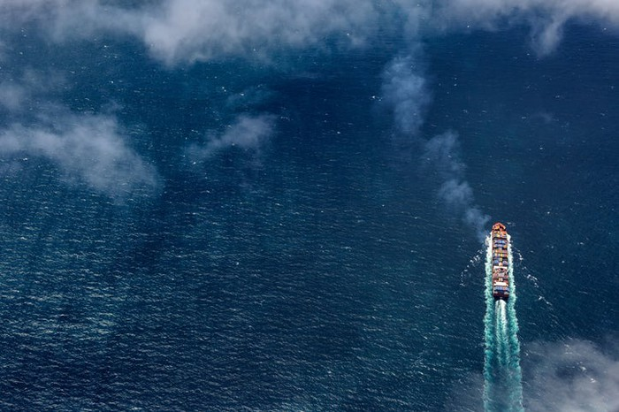 An aerial view of a cargo ship on the open ocean.