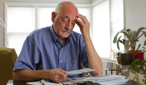 Senior man looking at bills worried -- GettyImages-179813059