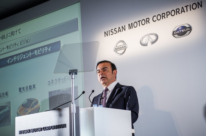 Ghosn is shown standing at a podium. Behind him, a backdrop with Nissan's logo.