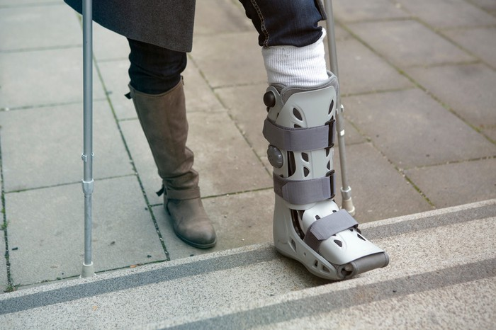 Legs only of a woman wearing a foot brace and using crutches.