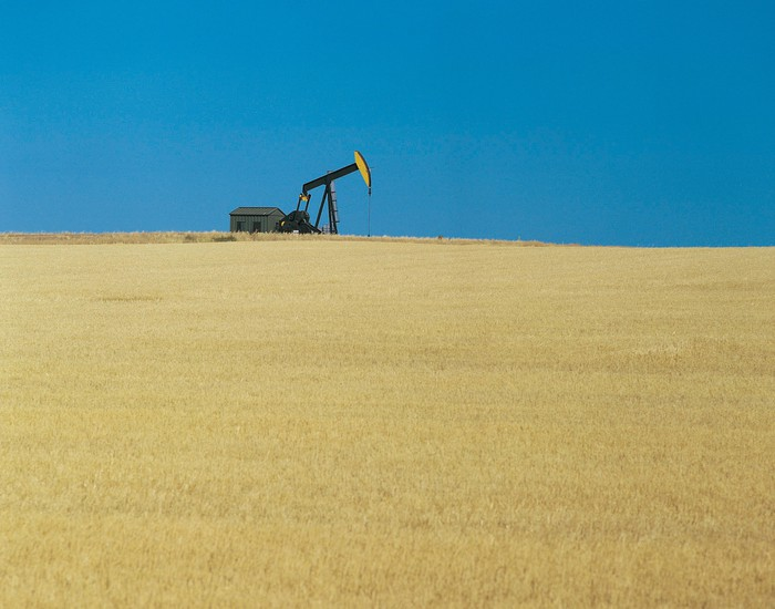 An oil pump on the horizon, with prairie in the foreground and blue sky behind it