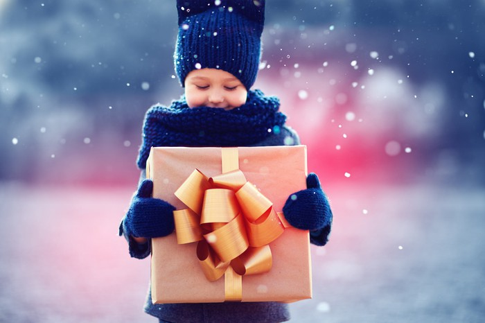 A boy holding a gift with a bow on it.