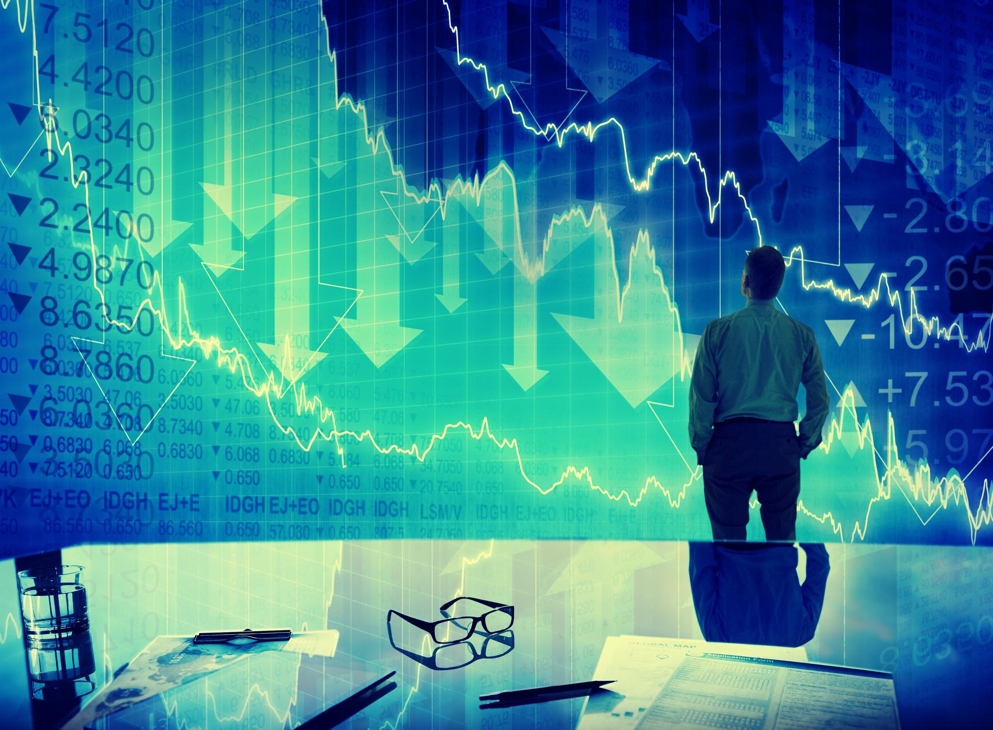 Man looking at display of falling stock graphs.