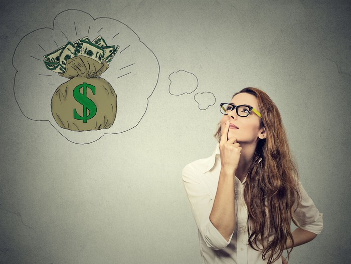 A bespectacled woman, with her forefinger on her lips, looking up at a thought bubble containing a bag with cash inside