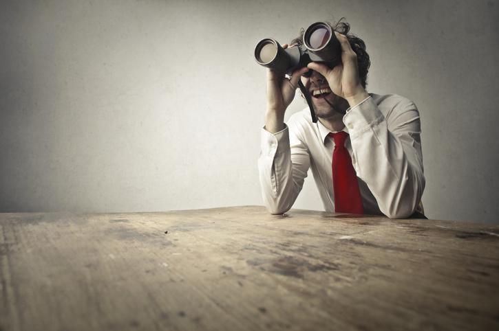 A businessman looking through binoculars.