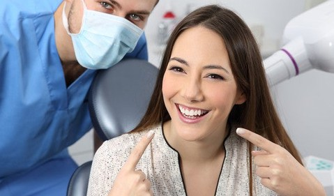 Dentist with smiling patient pointing at her teeth