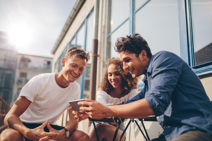 Three people sitting outside and looking at one smartphone.