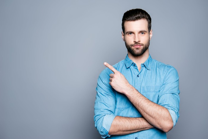 Confident man making pointing motion against a gray background