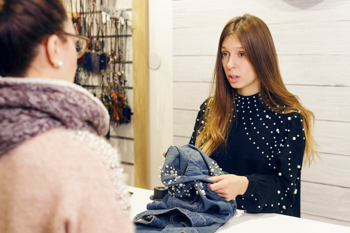 A clerk holds a pair of jeans in a clothing shop.