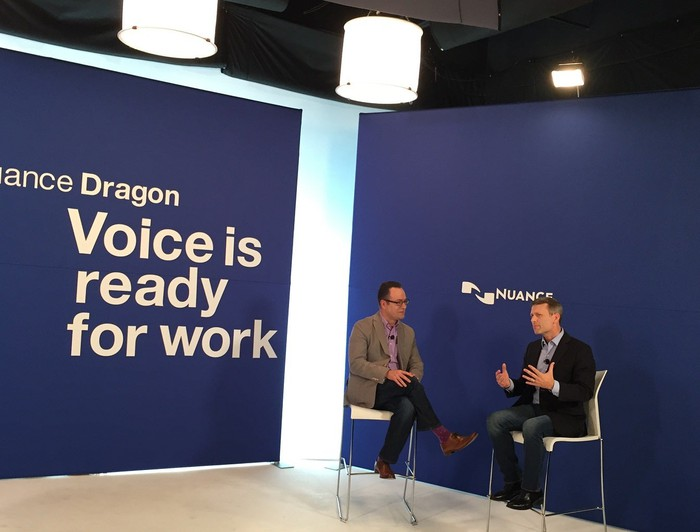 Two people on a stage with a backdrop with the Nuance logo and a slogan for the Dragon product line.