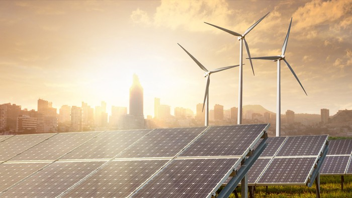 Wind and solar projects with a sunny city skyline in the background.