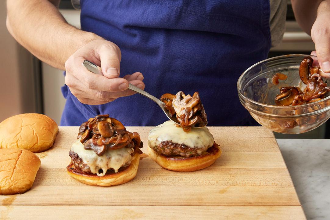 Man preparing a Blue Apron mushroom cheeseburger