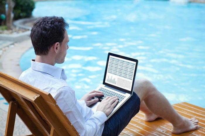 Man on laptop at pool