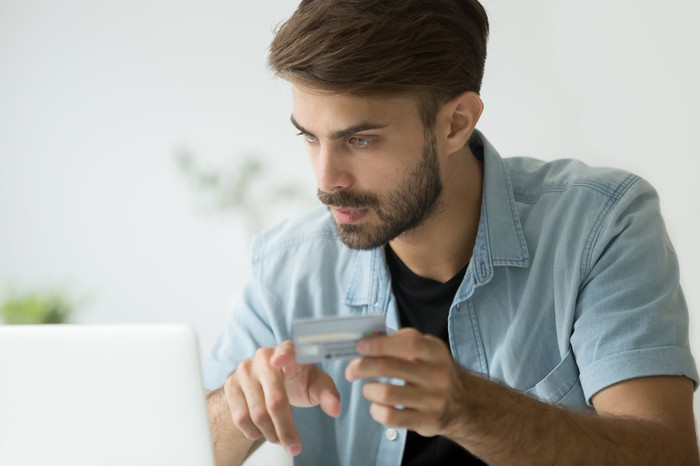 Young man at laptop with credit card