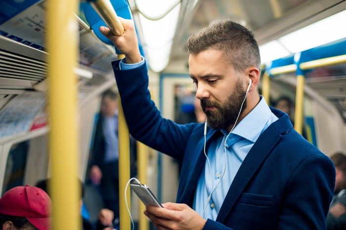 Man with headphones looking at his phone and holding onto train pole.
