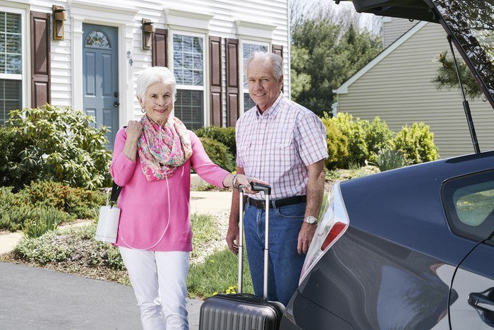 Woman wearing a shoulder-slung Inogen portable oxygen producer while holding a rolling carry-on suitcase and standing next to a senior man and his car.