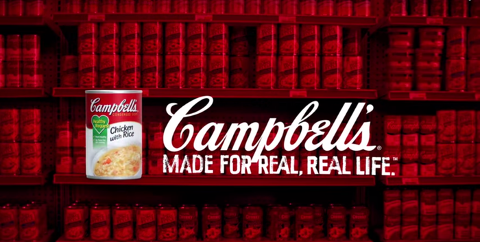 Campbell soup can in front of library of books, with Campbell logo.