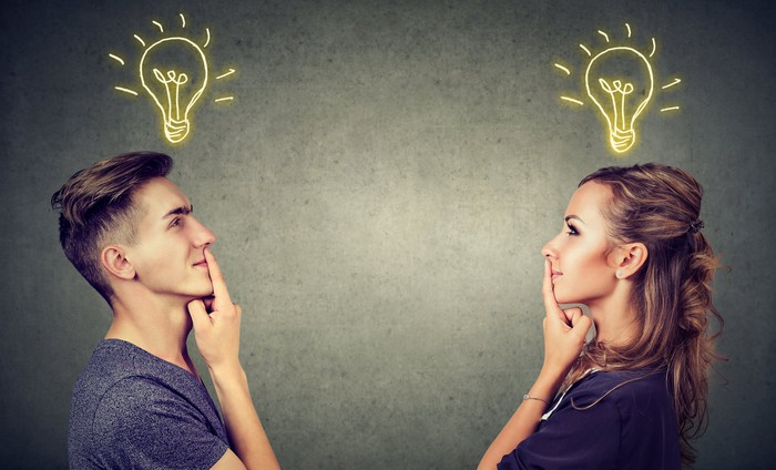 A man and woman facing each other, holding their fingers to their lips with light bulbs shining brightly above them.