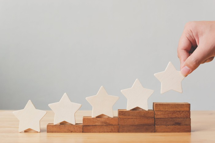 Five wooden stars on top of five ascending wooden stacks.
