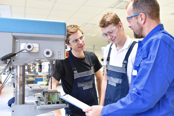 Older man wearing protective eyewear talking to two younger males wearing aprons and protective eyewear near machinery