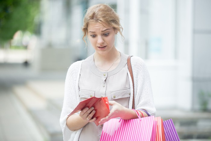 Woman looking nervously at wallet while carrying shopping bags