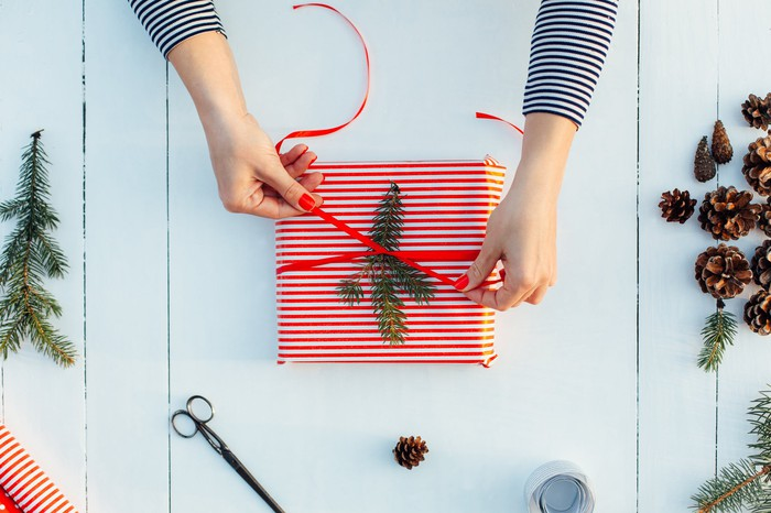 Woman tying bow on wrapped gift