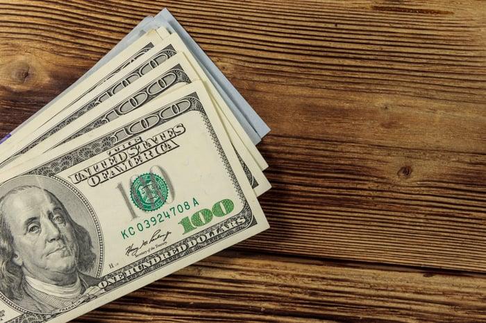 Stack of hundred-dollar bills on wooden surface.