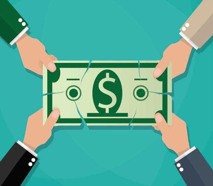 Four hands pulling apart a dollar bill