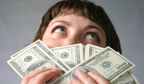 woman smelling 100 bills --GettyImages-101749466