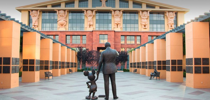 A statue of Walt Disney and Mickey Mouse holding hands in the middle of a path to the entrance of a Disney building.