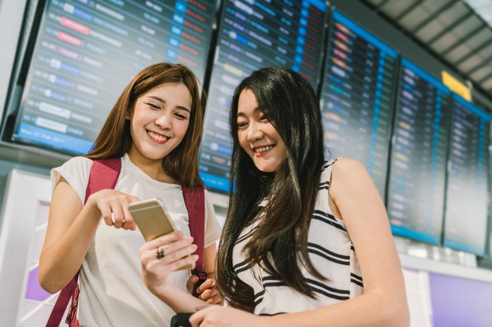 Two Asian girls smiling at a phone in front of a large information board