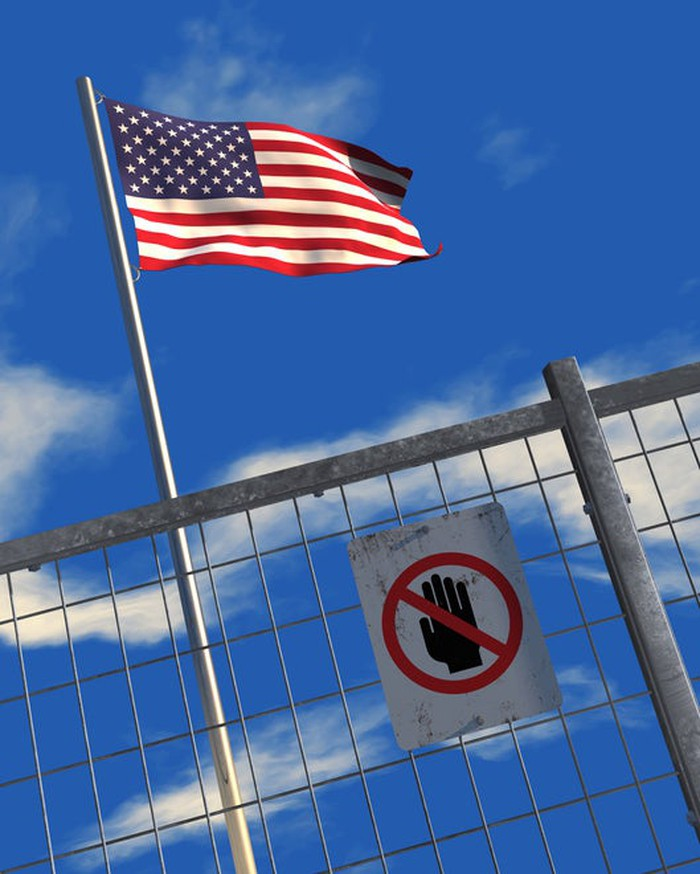 U.S. flag behind a metal fence with a keep-out sign posted on it.