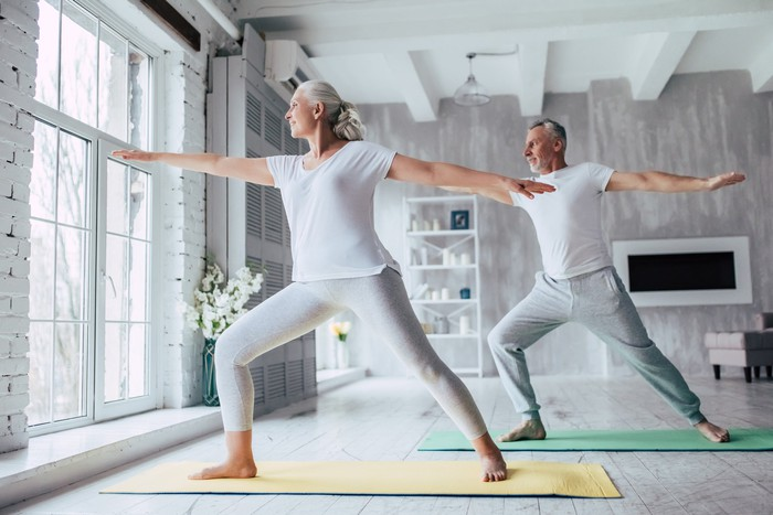 A senior couple doing yoga on mats in their home.