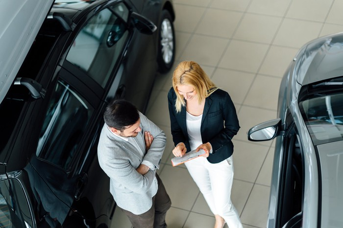 A woman and a man holding papers between two cars at a dealership.